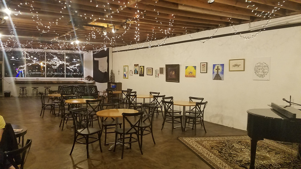 Coffee shop with tables, artwork, piano, and Christmas lights hanging from ceiling