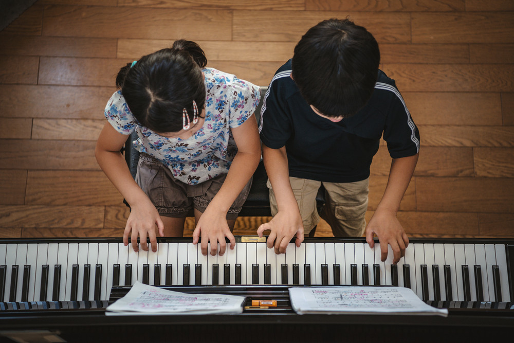A girl and boy young piano students playing a piano duet