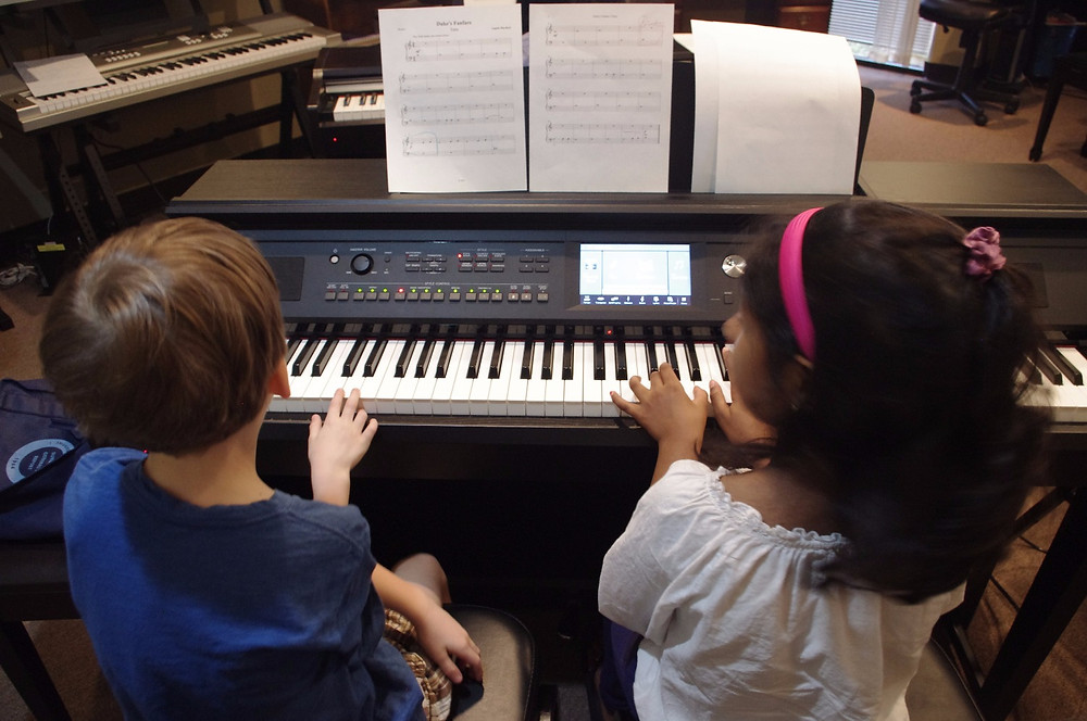 Piano students playing a duet on a Yamaha clavinova