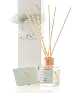 A 100ml reed diffuser containing essential oils, with 6 natural fibre reeds, standing next to a luxury branded gift box with pure silk ribbon bow and a branded business card.