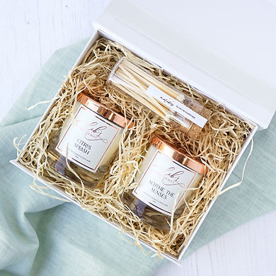 a flatlay of a candle and matches set presented in a luxury gift box