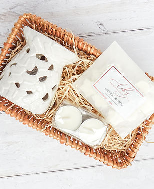A home fragrance gift set presented in a wicker basket on a painted wooden surface. The basket contains a bag of 12 scented wax melts, 2 unscented soy tealights and a butterfly embossed oil burner, wax melter.