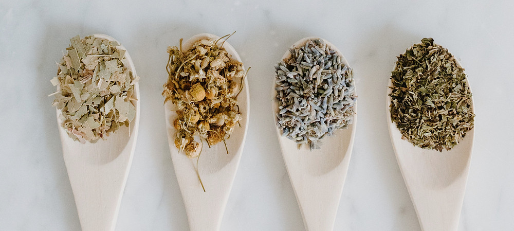 Dried flowers and herbs in four wooden spoons