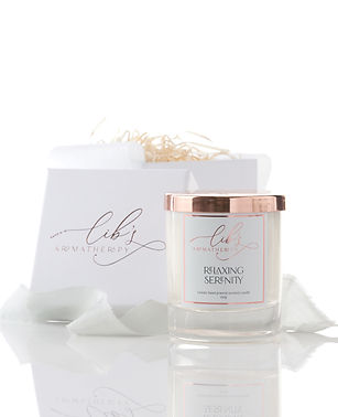A natural soy candle containing lavender and geranium essential oils. The candle is set on a reflective surface in front of a luxury branded gift box