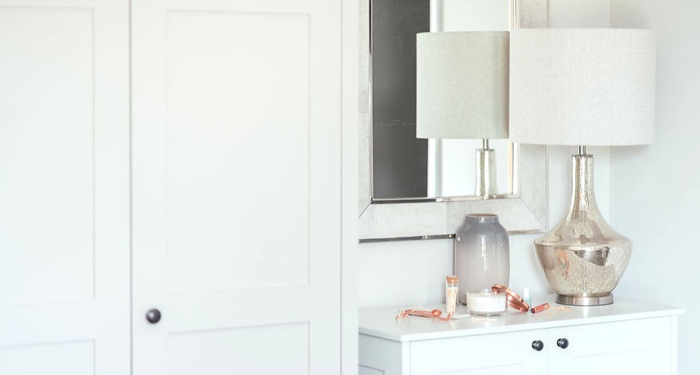a bedroom dressing table styled with a candle and some cosmetics