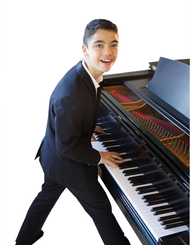 Ethan Bortnick Standing at Piano.png
