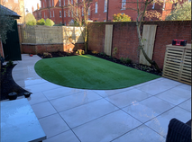 Atifical lawn with grey porcelain paving and contemporary fencing