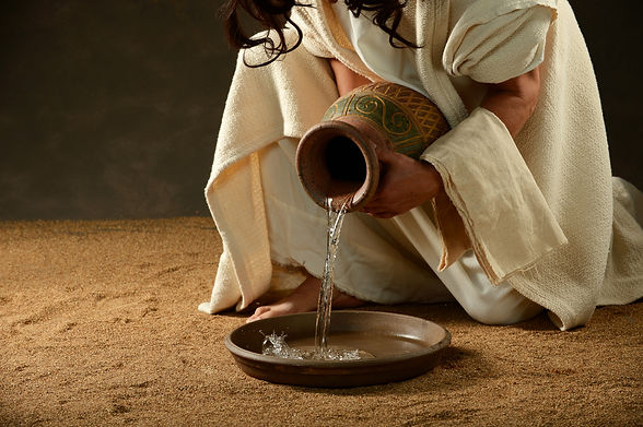Jesus pouring water from a jar before washing his disciples feet.jpg