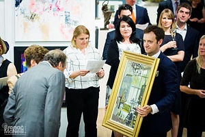 A painting being held up during the live auction