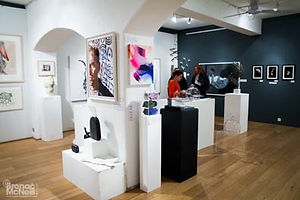 Sculptures on plinths with other art in the background