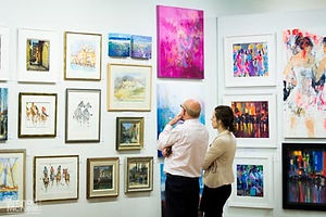 Man and woman looking at a wall of paintings