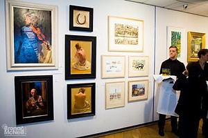 Waiter stood near a wall of paintings