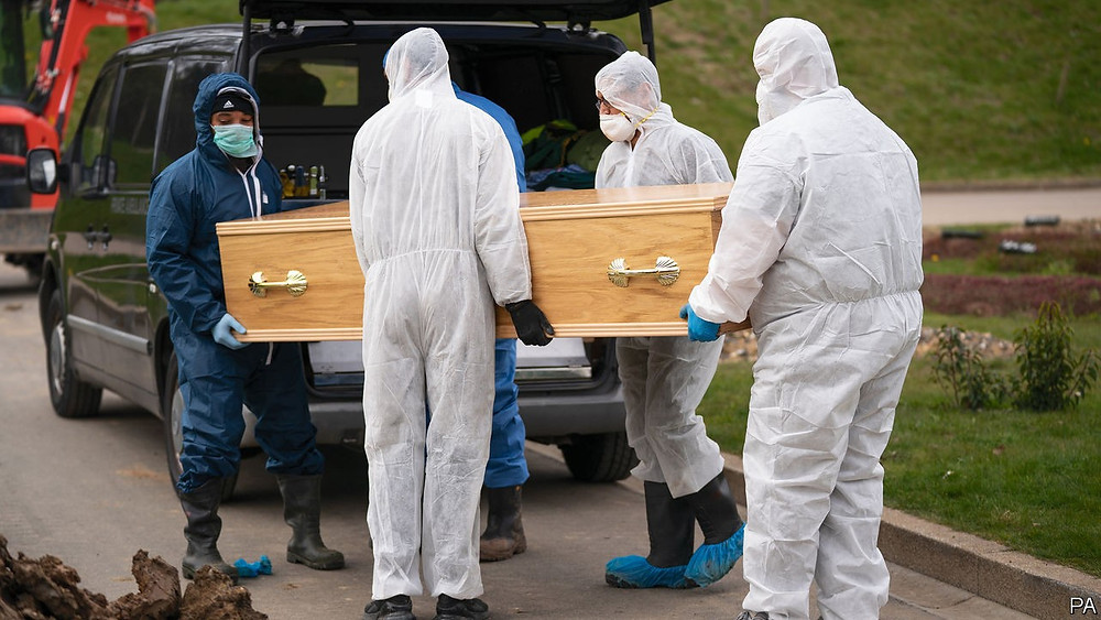 People wearing PPE and holding a coffin for a funeral during Covid 19