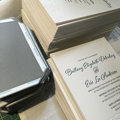 Double thick letterpress wedding invitations during assembly, by Lucky Invitations.