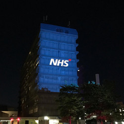 The NHS Animated Logo with a heart projected onto the Gloucester Royal Hospital by Evenlode Films an