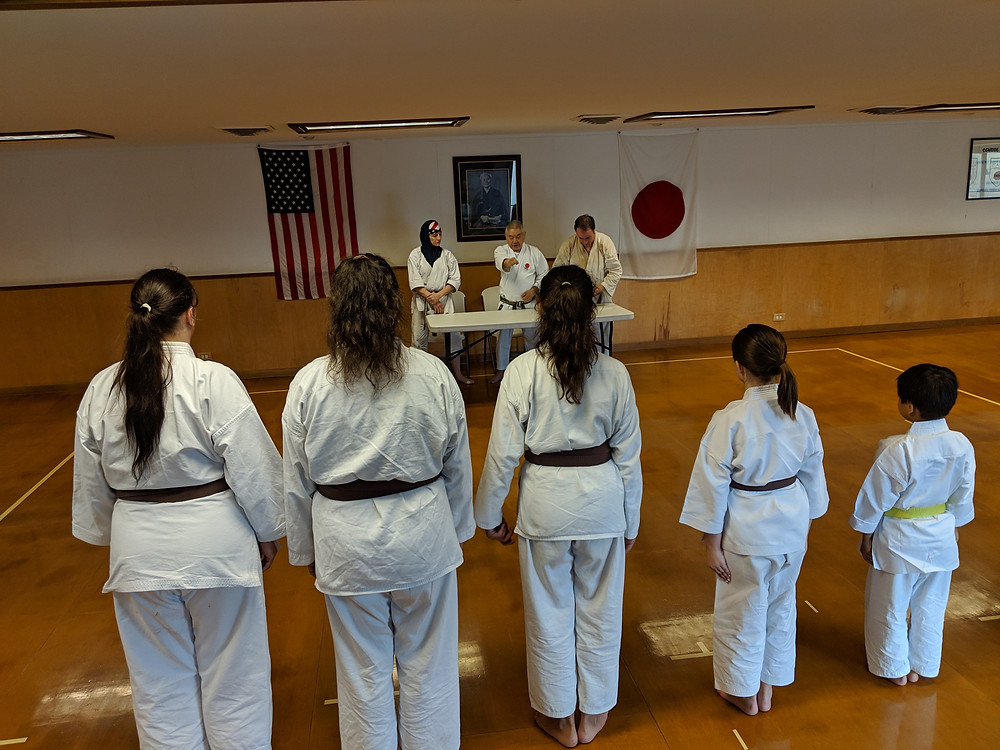 Sensei Mikami teaches finer points of punching technique to students during rank test in Metairie.
