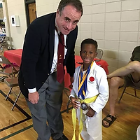 Youth karate class instructor proud of h