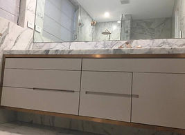 Marble sink and walls in a modern bathroom. Cabinets undernead sinnk are white with a gold chrome trim
