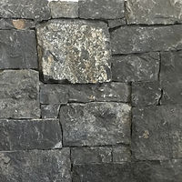 Natural stone wall cladding in random sizes, dark charcoal in colour with a bumpy and uneven surface