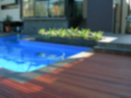 Backyard with pool, timber decking and charcoal plant box jutting out into the pool