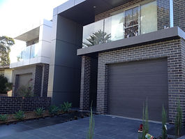 The front of a modern duplex with dark bricks, black pavement on the driveway and a glass balcony above a garage