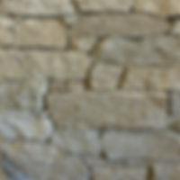 Cobblestone wall cladding of random sizes, mottled light grey in colour