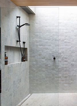Grey stone look with small square mosaic tiles in a shower recess.