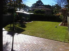 A flat backyard with bricks leading to grass