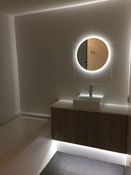 Modern bathroom with an oval mirror with an LED light behind it