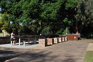 Park bench in a sitting area, next to a bbq and brick cubes to sit on