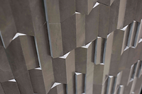 Smooth grey Jagged interlocking rectangular tiles, forming a raised uneven surface