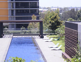 A swimming pool built into a balcony overlooking an appartment complex