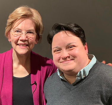 Image of Elizabeth Warren holding arm over Jossie Valentin and smiling together into the camera.