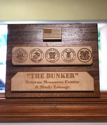 "Wooden plaque titled ""The Bunker"". This plaque sits outside of the Veteran Resource Center and Study Lounge"