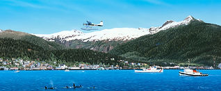 Bush plane flies along waterfront in Ketchikan, Alaska