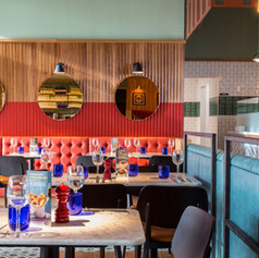 Coral leather upholstered banquette seating creates a relaxed dining space