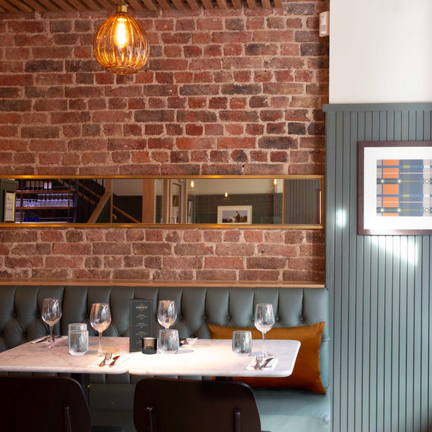 Lichen wall panelling & leather banquettes contrast beautifully with the original brickwork at this welcoming pub