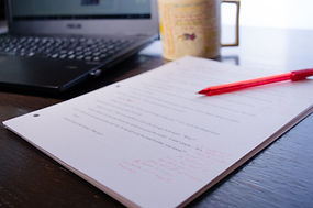 Papers with developmental edit and red pen