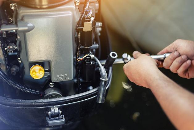 mechanic repairing inflatable motorboat