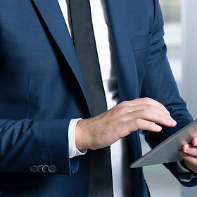 businessman-in-suit-using-tablet-PPJUNZD