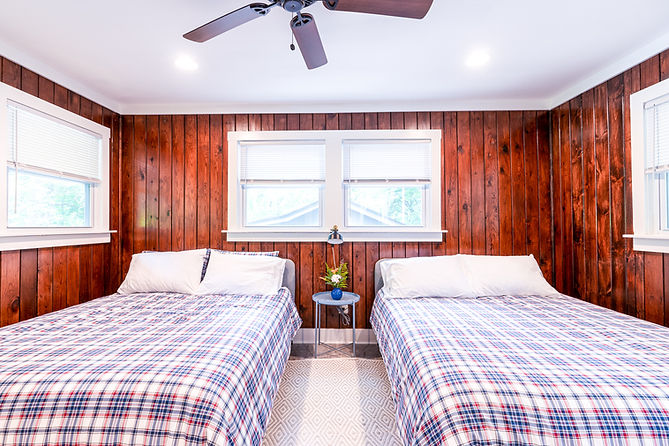 The bedroom inside of a Foggy Bottom cabin. The wall has wood paneling with a white window. There are two queen beds with plaid comforters and a small bedside table in between them.
