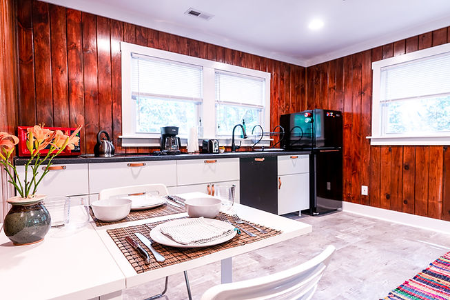 The interior of a cabin at Foggy Bottom Cabins. The shot looks into the kitchen with a set dining room table, white cabinents, and wood paneling.