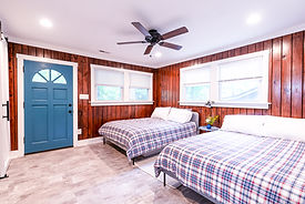 The bedroom inside of a Foggy Bottom cabin. The wall has wood paneling with two white windows. There are two queen beds with plaid comforters and a small bedside table in between them.There is also a blue door that leads to the front porch.