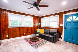 The living room extends off the kitchen inside the cabins. There is a brown leather couch with decorative pillows, a circular coffee table, and colorful striped rug in the room.
