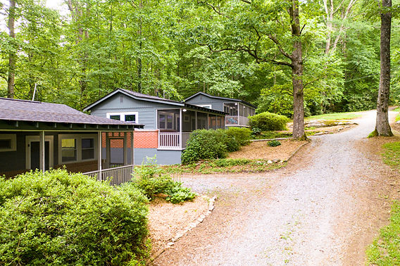 The exterior of all three blue cabins, including the gravel driveway and light green tree canopy over the cabins.