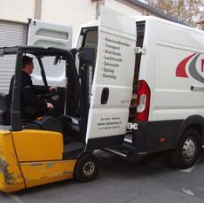 Heftruck lossing MJT Logistics bus