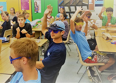 high school students raisin their hands in class