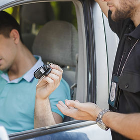 Young man driver pulled over by cop and handing over his keys