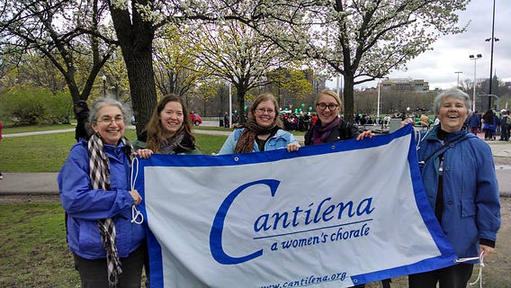 "Cantilena singers at the Walk for Music, smiling and holding a banner that says ""Cantilena, a women's chorale"""