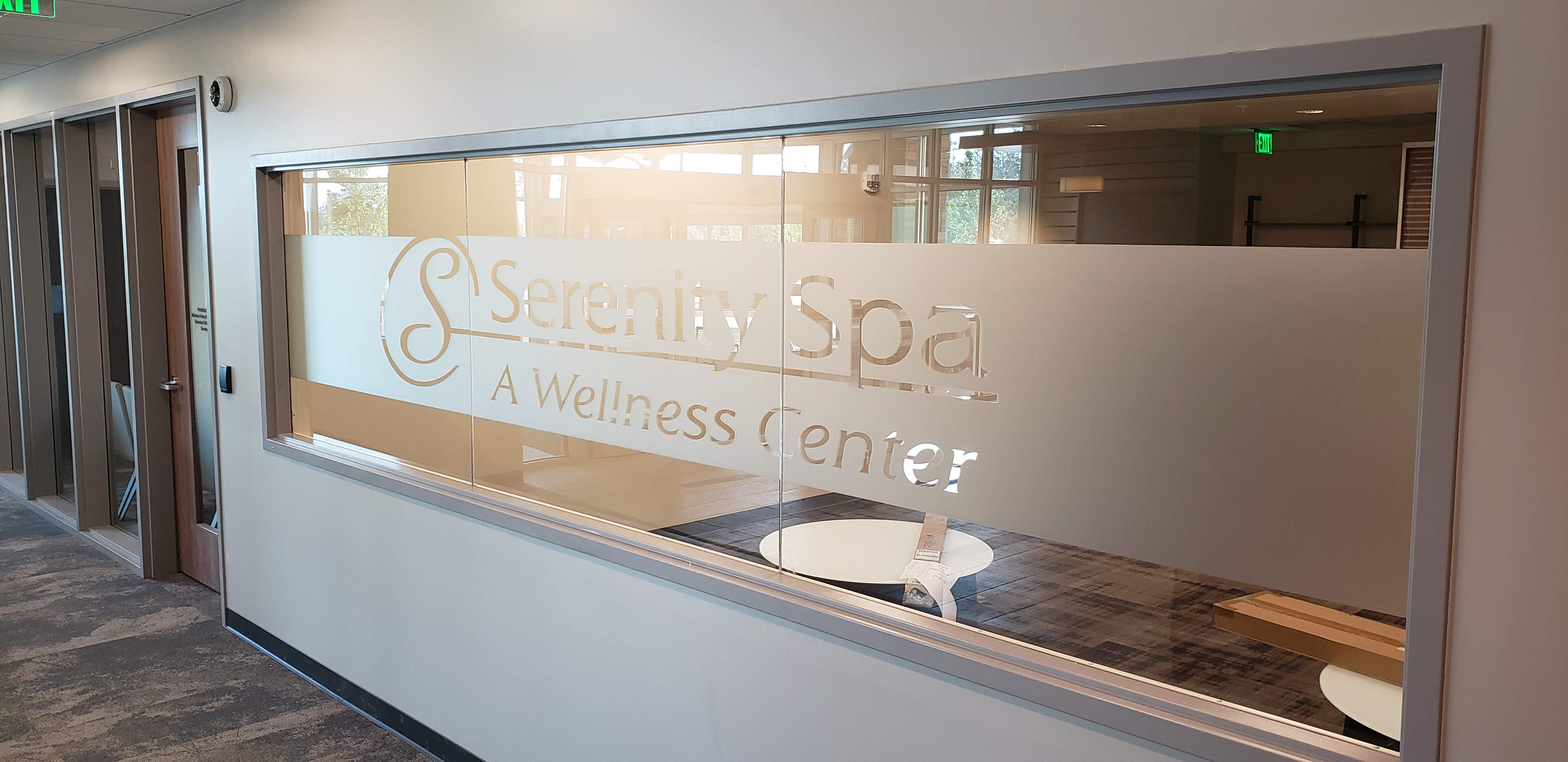 A spa and wellness center with a precision cut decorative film logo spanning multiple panes of glass